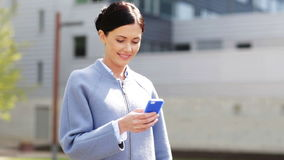 Smiling businesswoman with smartphone texting stock footage