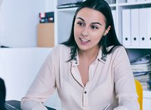 Smiling businesswoman speaking with costumer in office. Young Smiling businesswoman speaking with costumer in office stock photography