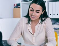 Smiling businesswoman speaking with costumer in office. Young Smiling businesswoman speaking with costumer in office royalty free stock image