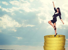 Smiling businesswoman standing on coins stack Stock Photo