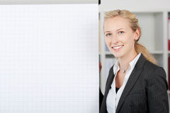 Smiling Businesswoman Standing By Flipchart In Office Royalty Free Stock Images