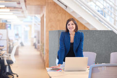Smiling businesswoman standing at her desk in bright modern offi Stock Photo