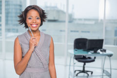 Smiling businesswoman standing in her office holding pen Royalty Free Stock Photography