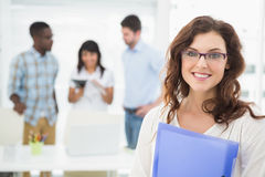 Smiling businesswoman standing and holding folder Stock Photography