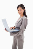 Smiling businesswoman standing with laptop Royalty Free Stock Image