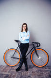 Smiling businesswoman standing near bicycle Stock Photos