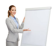 Smiling businesswoman standing next to flipboard Stock Photo
