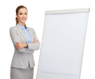Smiling businesswoman standing next to flipboard Stock Photography