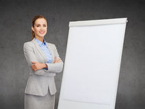 Smiling businesswoman standing next to flipboard Stock Photos