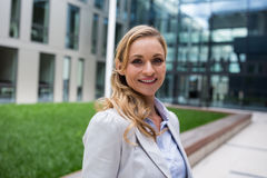 Smiling businesswoman standing in office premises. Portrait of smiling businesswoman standing in office premises Stock Photography