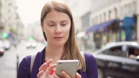 Smiling businesswoman standing on street using smartphone. Professional female browsing reading news. Positive businesswoman standing on street using mobile stock video footage