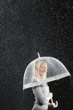 Smiling businesswoman Standing Under Umbrella during rain Royalty Free Stock Images
