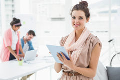Smiling businesswoman standing and using tablet Royalty Free Stock Photography