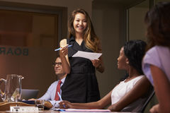 Smiling businesswoman stands presenting to team at meeting Stock Image