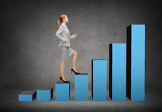 Smiling businesswoman stepping on chart bar Stock Images