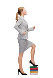 Smiling businesswoman stepping on pile of books Royalty Free Stock Photos