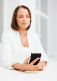 Smiling businesswoman or student with smartphone Stock Images