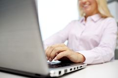 Smiling businesswoman or student typing on laptop Royalty Free Stock Photo