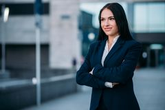 Smiling businesswoman in suit, business center. Portrait of smiling businesswoman in suit, business center on background. Modern financial building, cityscape Stock Image