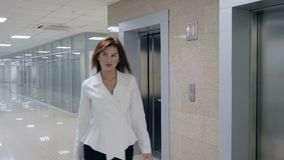 Smiling businesswoman in suit stepping out of elevator