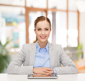 Smiling businesswoman with tablet pc. Business, technology, education and people concept - smiling businesswoman sitting at table with tablet pc computer over Stock Photography