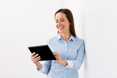 Smiling businesswoman with tablet pc computer. Business, people and technology concept - smiling businesswoman with tablet pc computer at office Royalty Free Stock Image