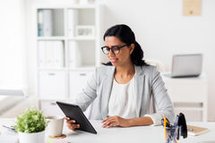 Smiling businesswoman with tablet pc at office. Business, people and technology concept - smiling businesswoman with tablet pc computer at office Stock Images