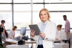Smiling businesswoman with tablet pc at office Royalty Free Stock Image