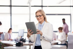 Smiling businesswoman with tablet pc at office Stock Image