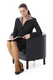Smiling businesswoman taking notes. Into personal calendar, sitting in armchair,  on white Stock Images