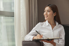 Smiling businesswoman taking notes and looking at the window Stock Photo