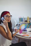 Smiling businesswoman talking on mobile phone while holding colour swatch Royalty Free Stock Photography