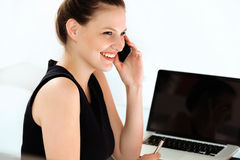 Smiling businesswoman talking on mobile phone in a office Stock Photos