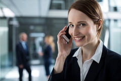 Smiling businesswoman talking on mobile phone in office corridor Stock Image