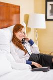 Smiling businesswoman talking on phone while sitting on the bed in hotel room. Stock Photos