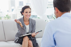 Smiling businesswoman talking to her colleague Stock Photos