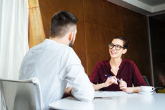 Smiling businesswoman talking to young businessman in meeting room Stock Photos