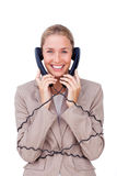 Smiling businesswoman tangled up in phone wires Stock Photo