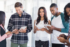 Smiling businesswoman with team using mobile phones and digital tablets. Smiling businesswoman standing with team using mobile phones and digital tablets at royalty free stock photos