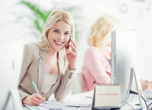 Smiling Businesswoman Telephoning at Work Royalty Free Stock Images