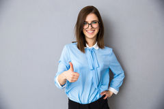 Smiling businesswoman with thumb up over gray background Stock Images