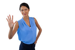 Smiling businesswoman touching interface while standing with hand on hip. Against white background Royalty Free Stock Photos