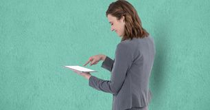 Smiling businesswoman touching screen of tablet PC over turquoise background Stock Photography