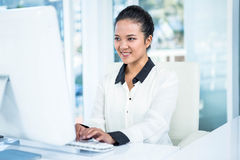 Smiling businesswoman typing on her computer Royalty Free Stock Images