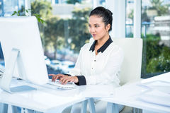 Smiling businesswoman typing on her computer Royalty Free Stock Photos