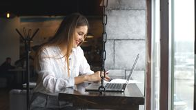 Smiling businesswoman typing on her laptop and uses a smartphone. Woman wearing white shirt smile and thinking in Coffee shop cafe with computer laptop on the stock video