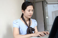 Smiling businesswoman typing on laptop Stock Images