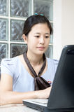 Smiling businesswoman typing on laptop Royalty Free Stock Image