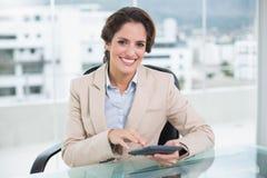 Smiling businesswoman using calculator Stock Photo