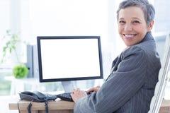 Smiling businesswoman using computer Stock Photos